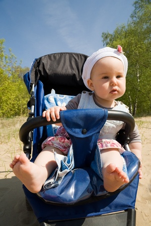 stroller: Baby girl sitting in the baby carriage in the forest