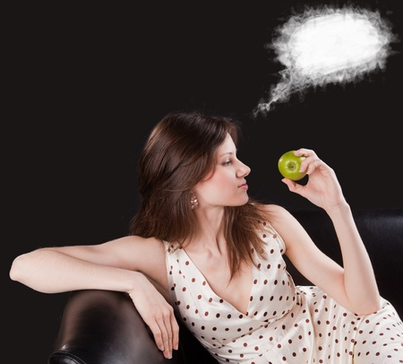 Young beautiful woman hold an apple and dream about something