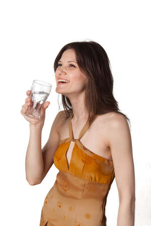 Young beautiful woman looking above a glass of sparkling water in her hand and smile