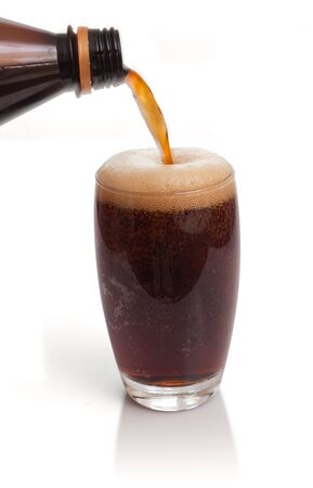 Glass of kvass with flow from bottle and froth Stock Photo