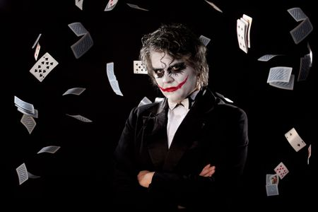 man in an image of a joker with fly cards on black background Stock Photo