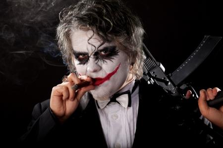 bad joker with submachine gun and cigar on black background