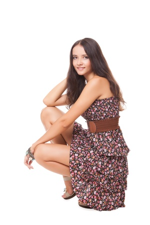 lovely bright young woman squatting on white background photo