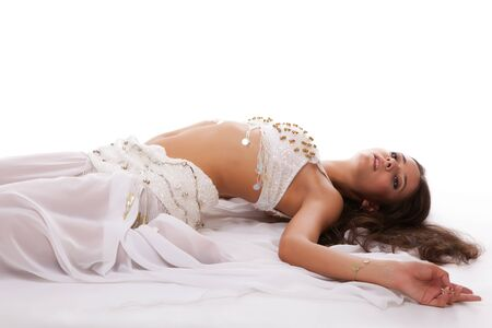 woman arabic belly dancer in white costume lying on the floor isolated on white background Stock Photo - 10222574