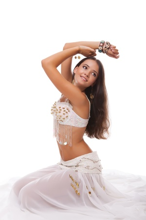 young woman belly dancer in white costume sitting on the floor isolated on white background Stock Photo