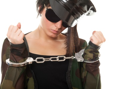 young woman police officer with handcuffs on white background photo