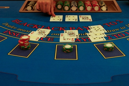 The dealer distributes cards on blackjack table in casino