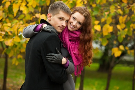young happy couple in the park. girl a hugging boyfriend.