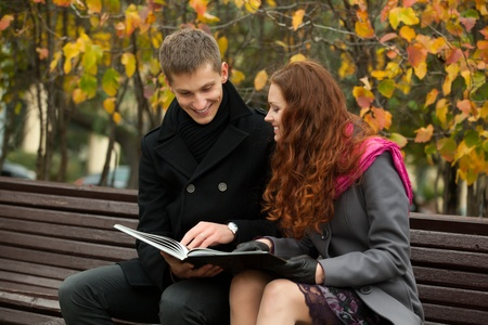 young happy couple with book on the bench. woman and man smiling. photo