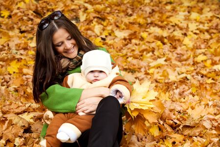 young mother holding baby in park. a bright autumn day. photo