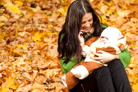 young mother with baby in park. a bright autumn day. photo