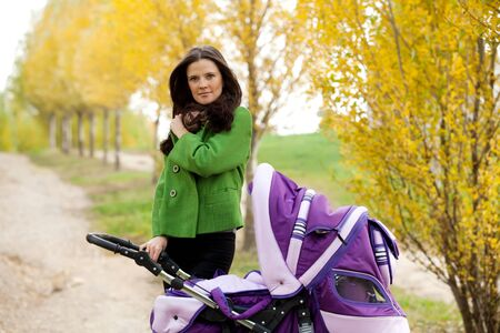 perambulator: close-up happy mom with stroller in autumn city park