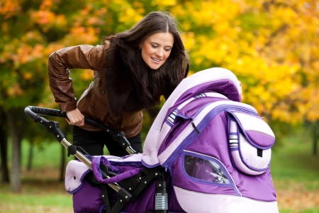 happy mom with stroller walks in park. a bright autumn day. Stock Photo
