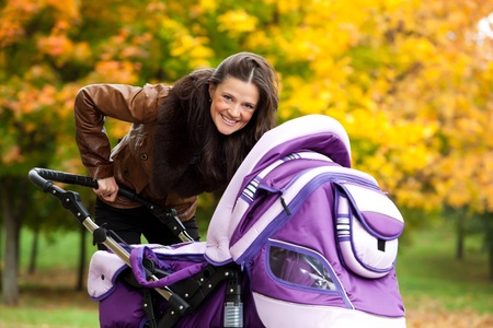 perambulator: young mother with baby in stroller walks in park. a bright autumn day.