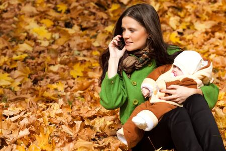 young mother with child in hand and talk on mobile phone photo