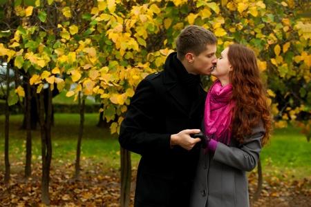 pareja besandose: Amor joven pareja bes�ndose en el fondo de los �rboles en oto�o Foto de archivo