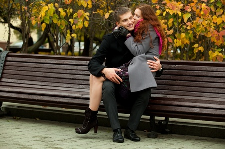 beautiful girl sits on her boyfriend knees in park bench Stock Photo