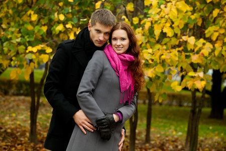 young man hugging his woman in autumn park