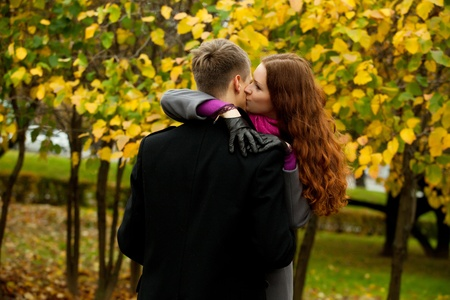 young woman kissing boyfriend in autumn park photo