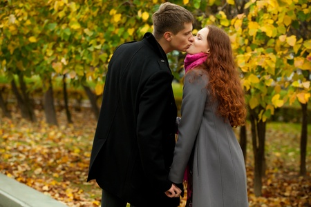 young woman and man kissing in autumn park