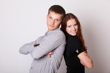 young couple with folded hands and look camera photo