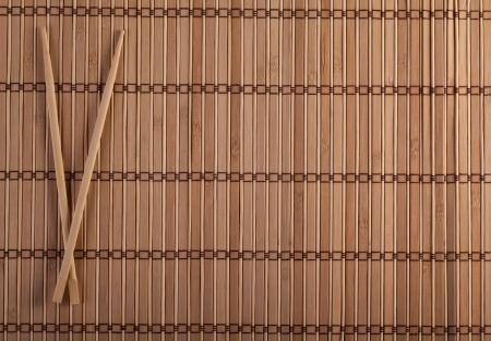 sushi menu: Two chopsticks on sushi mat background for menu