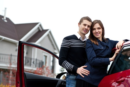 campagna: giovane famiglia di successo vicino alla macchina contro la sua casa