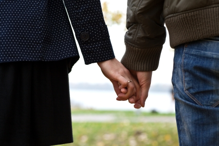 man and woman holding hands with each other, outdoors