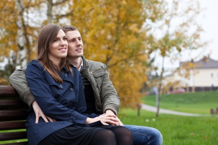 countryside loving: young couple sitting on bench in autumn park, outdoors