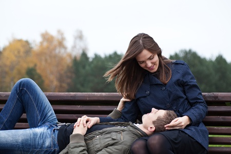 on lap: man lying in lap of young woman on park bench Stock Photo