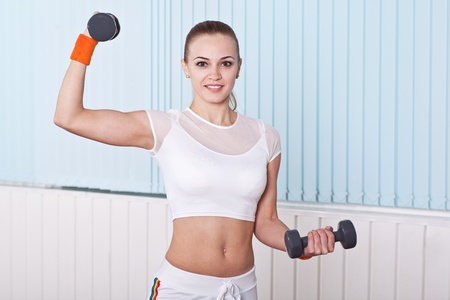 fitness woman lifting dumbbells in sport hall photo