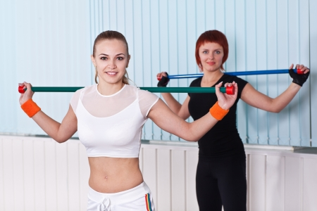 two fitness women doing exercises in sport club