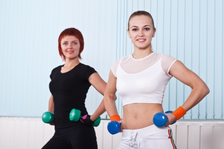 two fitness women with hand weights in sport hall photo