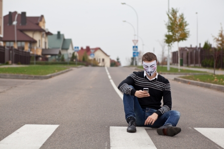 hacker in masked members of Anonymous with mobile phone