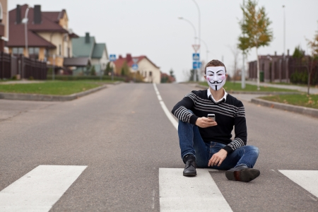 spammer: hacker in masked members of Anonymous with mobile phone looking at camera Editorial