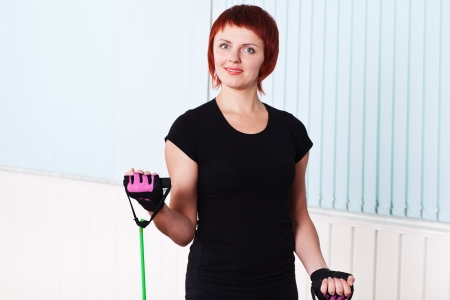 expander: redhead fitness woman doing exercise with expander for biceps