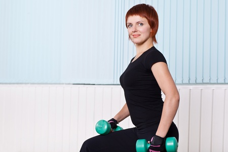 young sport woman with dumbbells in gym photo