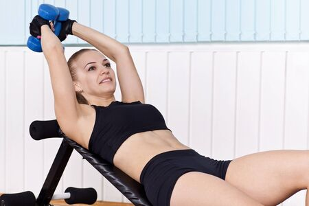 incline: closeup woman training with dumbbells on incline bench