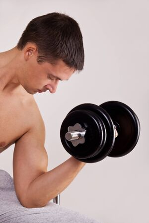 handsome man uses dumbbells to exercise flexing biceps muscle photo