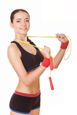 young woman with healthy sporty figure holding skipping rope photo
