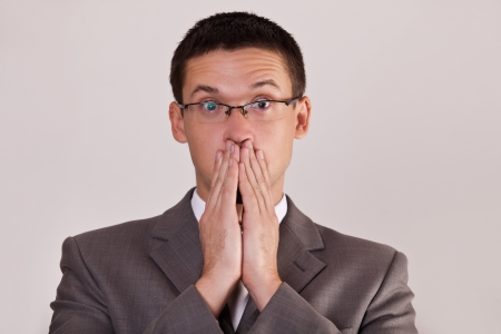 halitosis: surprised men covered his mouth hand on gray background
