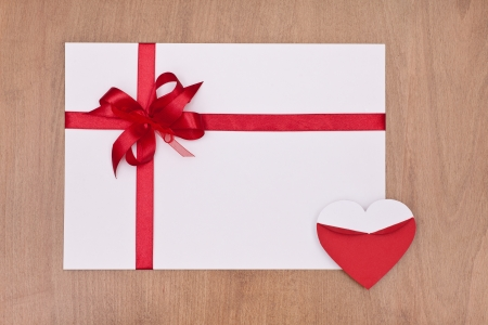 blank valentine card with red ribbon and red heart on wooden background photo