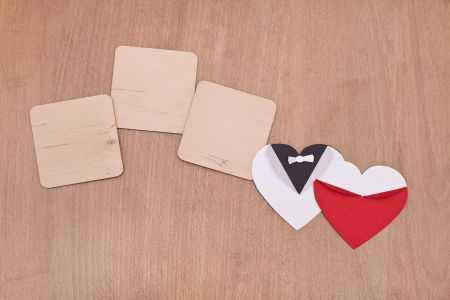 blank wooden sign with white and red hearts on wooden background photo
