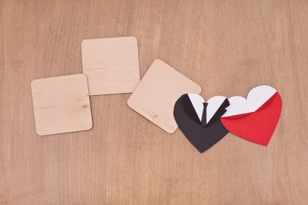 three empty wooden boards with black and red hearts on wooden background photo