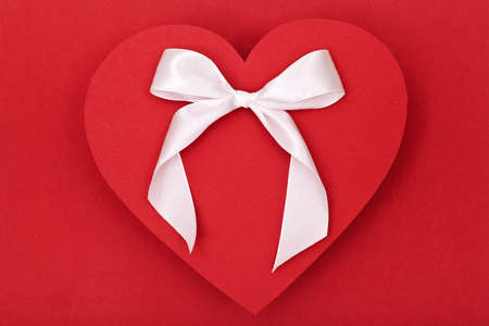 red heart and white bow on red background, valentines day theme photo