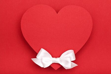 valentines day background red heart and white bow on red background photo