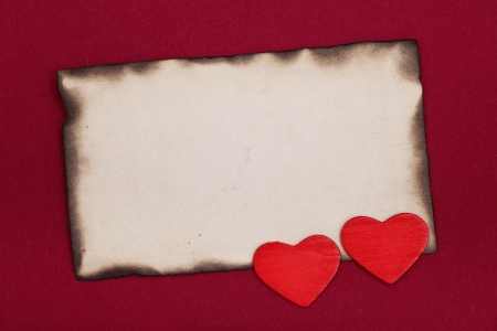 blank old burnt paper and two hearts on red background photo