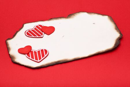 empty grunge burnt paper and hearts on red background photo