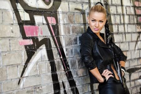 beautiful modern woman near brick wall with graffiti