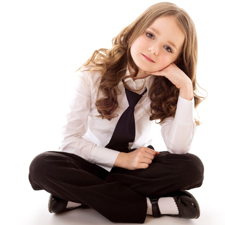 little business girl sit and looks forward isolated on white background